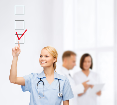 checkbox: healthcare, medical and technology - young doctor or nurse with marker drawning red checkmark into checkbox with team on the back