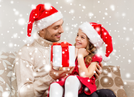 family, christmas, x-mas, winter, happiness and people concept - smiling father giving daughter gift box photo