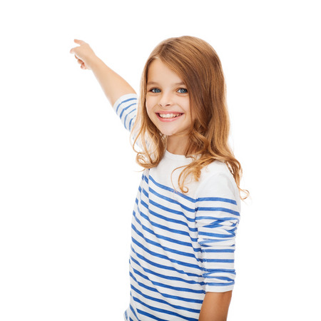 picking fingers: education, school and virtual screen concept - cute little girl pointing in the air or virtual screen