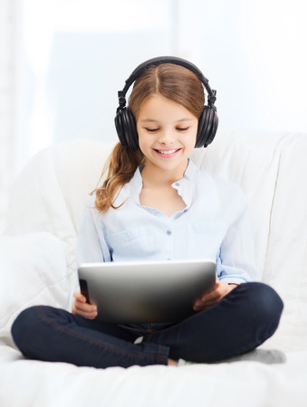 home, leisure, new technology and music concept - smiling little girl with tablet pc computer and headphones at home photo