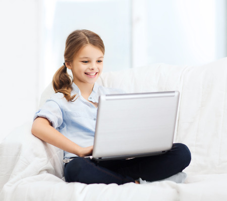 home, leisure, technology and internet concept - little student girl with laptop computer at home photo
