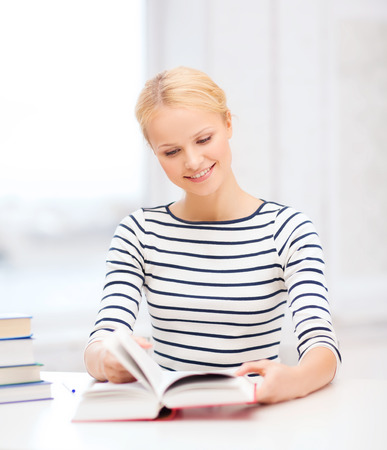education, school and business concept - smiling woman with books and notebook studying in college photo