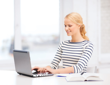 business, education and technology concept - smiling student with book, laptop computer and notebook in college Stock Photo - 24109072