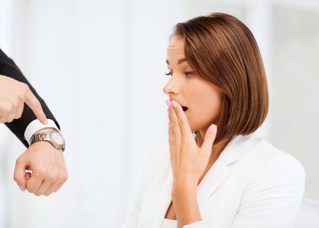 business and time management concept - boss showing watch to stressed businesswoman Stok Fotoğraf