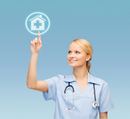 healthcare, medicine and technology concept - smiling young doctor or nurse pointing to hospital icon Stock Photo