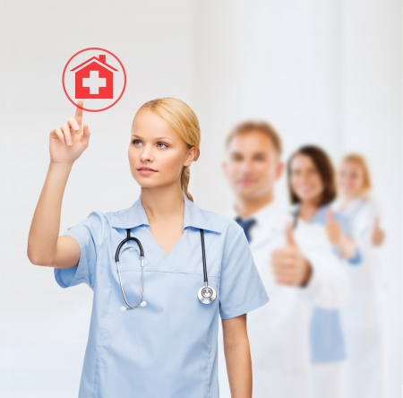 new medicine: healthcare, medicine and technology concept - smiling young doctor or nurse pointing to red hospital icon Stock Photo