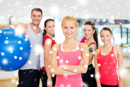 fitness, sport, training, gym and lifestyle concept - smiling woman standing in front of the group of people in gym photo