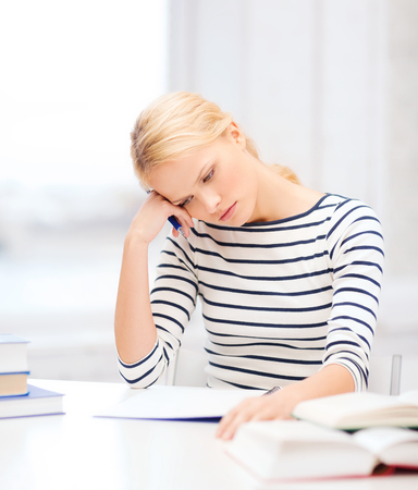 education, school and business concept - concentrated woman with books and notebook studying in college Stock Photo