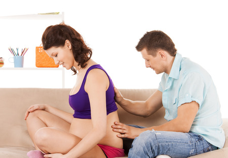 health woman: health, pregnancy and happy people concept - husband giving his wife back massage at home
