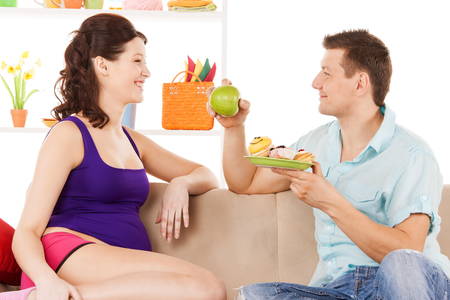 pregnancy and healthy eating concept - happy expecting parents at home photo
