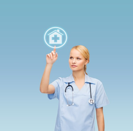 healthcare, medicine and technology concept - smiling young doctor or nurse pointing to hospital icon photo
