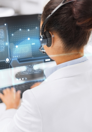computer operator: business, communication and call center concept - friendly female helpline operator with headphones and computer Stock Photo