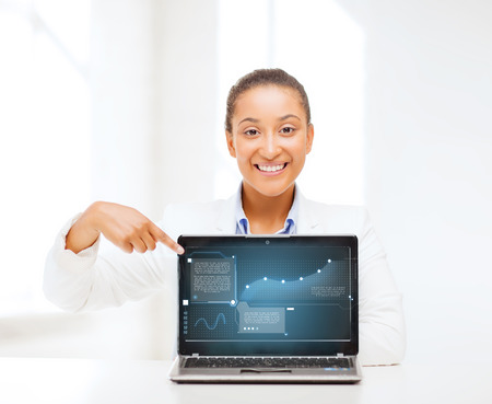 business, new technology and internet concept - smiling woman with laptop computer photo