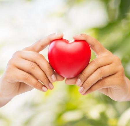 Gesundheit und Wohltätigkeits Konzept - Nahaufnahme von Frau Hände mit Herz