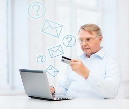 shopping questions: business, online banking, internet shopping and oldness concept - smiling old man with laptop computer and credit card at home