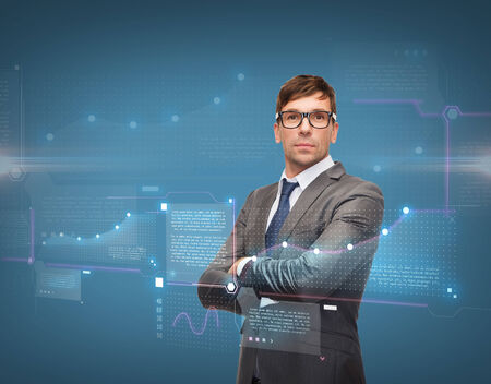 business, new technology and office concept - attractive buisnessman or teacher in glasses with charts on virtual screen photo