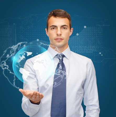 business, office and new technology concept - friendly young buisnessman holding virtual sphere globe on the palm of his hand photo