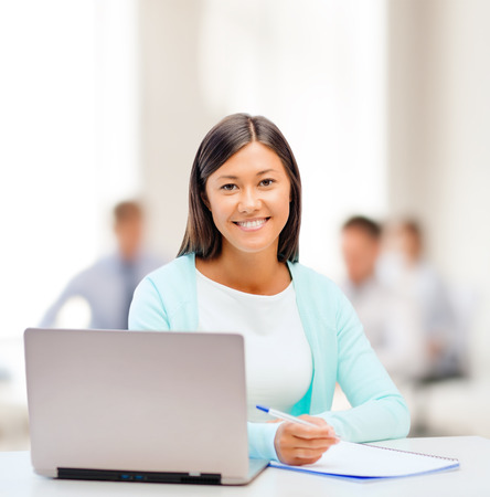 business, education and technology concept - asian businesswoman or student with laptop and documents in office photo