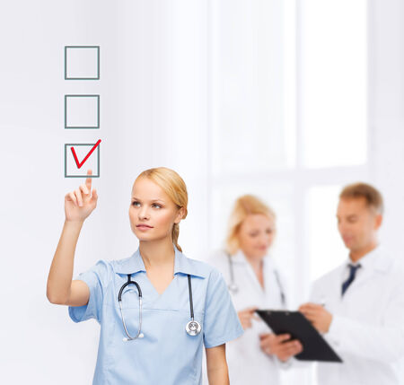 new medicine: healthcare, medicine and technology concept - smiling young doctor or nurse pointing to red checkmark in checkbox