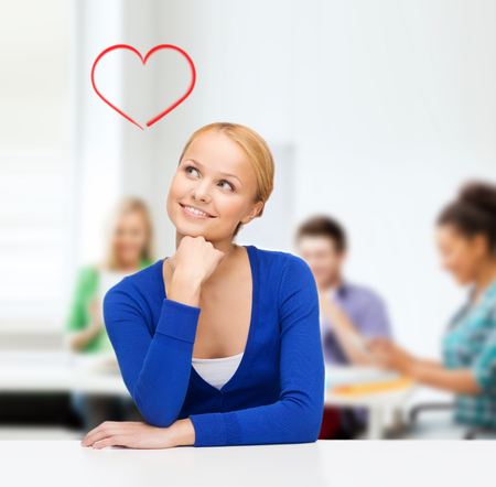 lecture room: hapiness, love, education, dating and people concept - happy smiling young woman dreaming