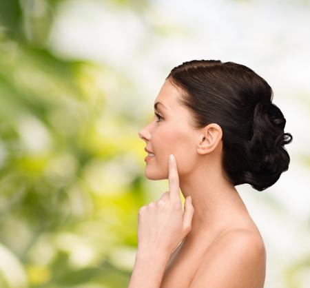 perfil de mujer rostro: belleza, spa y el concepto de salud - mujer joven y sonriente apuntando a la mejilla