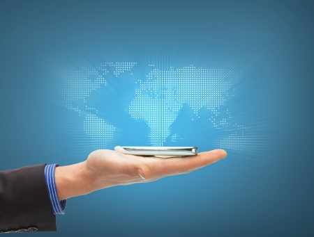 business, new technology and office concept - closeup of man hand with smartphone and virtual world map photo