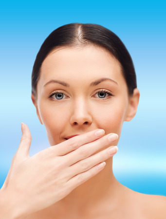 spa, health and beauty concept - beautiful woman covering her mouth photo