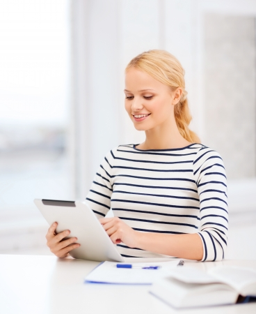 business, education and technology concept - smiling student with book, tablet pc computer and notebook in college photo
