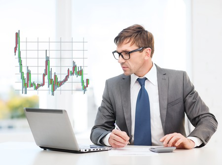 business, office and money concept - businessman in suit and black eyeglasses with laptop computer, papers, calculator and forex chart photo