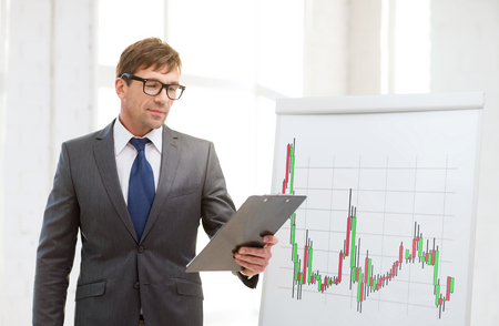 business, office and money concept - businessman in suit and black eyeglasses with clipboard and flip board with forex chart in office photo