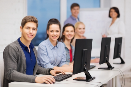 informatics: education, techology and internet concept - group of smiling students with computer monitor at school