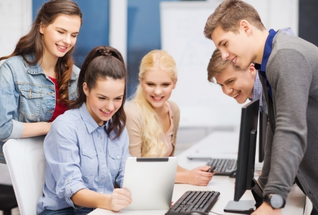 education, techology and internet concept - group of smiling students with computer monitor and tablet pc photo