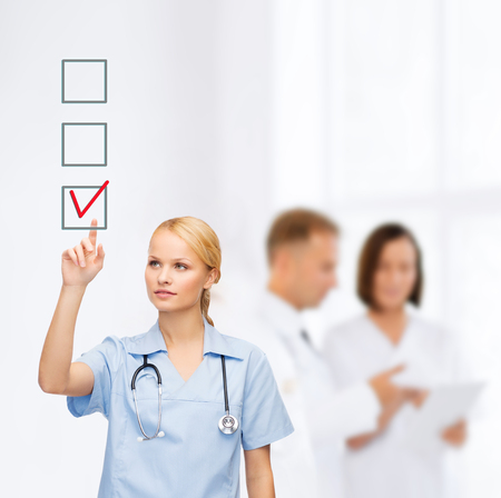 checkbox: healthcare, medicine and technology concept - smiling young doctor or nurse pointing to red checkmark in checkbox