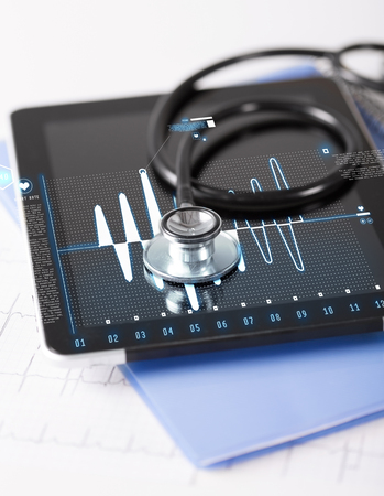 healthcare, medicine and technology concept - tablet pc, stethoscope and electrocardiogram photo