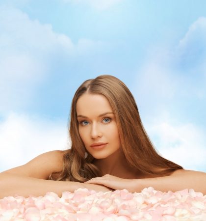 health and beauty concept - beautiful woman with long hair and rose petals photo