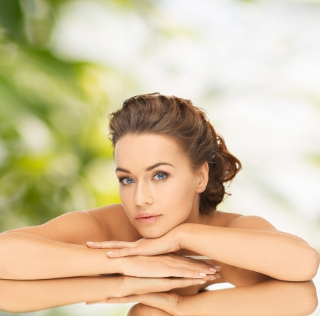 health and beauty concept - dreaming woman with updo and mirror Stock Photo