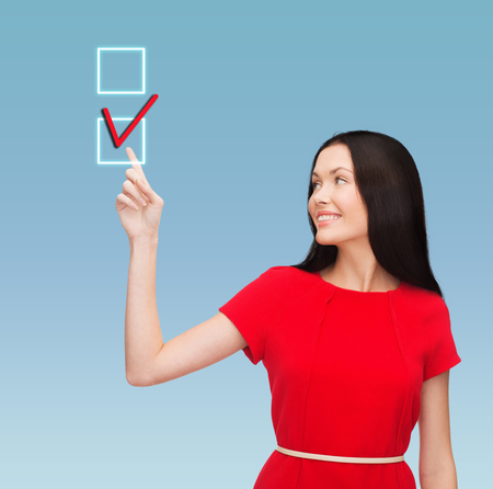 education and business concept - attractive young woman in red dress pointing her finger at red checkmark in checkbox photo