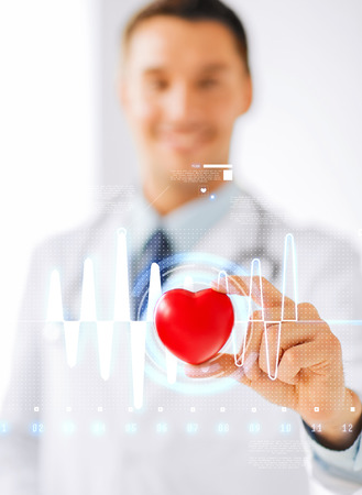 healthcare and medicine concept - male doctor with heart and cardiogram photo