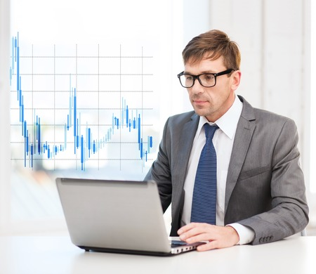 technology, money, business and office concept - handsome businessman in black eyeglasses with laptop computer and forex chart photo