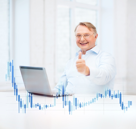 technology, money, oldness and lifestyle concept - old man in eyeglasses with laptop computer and forex chart at home showing thumbs up photo