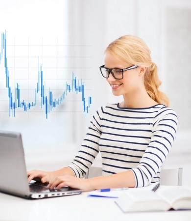 business, education, money and new technology concept - smiling student with laptop, book, computer, notebook, eyeglasses and forex chart photo