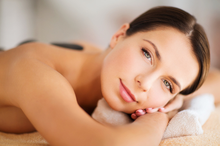 health and beauty, resort and relaxation concept - beautiful woman in spa salon with hot stones photo