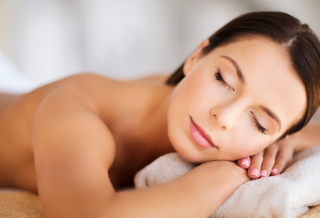 health and beauty, resort and relaxation concept - beautiful woman with closed eyes in spa salon lying on the massage desk photo