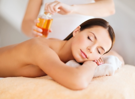 body oil: beauty, spa, resort and relaxation concept - beautiful woman in spa salon