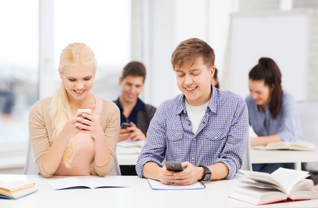 education and technology concept - group of students looking into smartphone at school photo