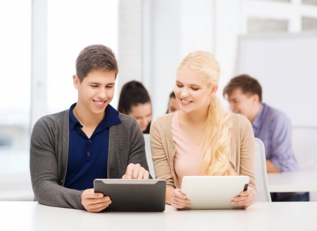 education, technology and internet - two smiling students looking at tablet pc in lecture at school photo