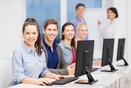 education, techology and internet concept - group of smiling students with computer monitor at school photo