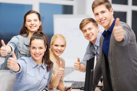 education, techology and internet concept - group of smiling students with computer monitor and smartphones photo