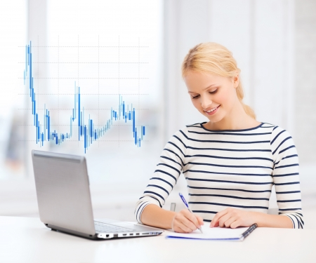 business, education, money and technology concept - smiling student with laptop computer, notebook and forex chart in college photo