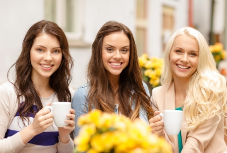 girlfriend: holidays, food and tourism concept - three beautiful girls drinking coffee in cafe Stock Photo